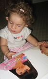 An infant girl is familiarizing herself with books