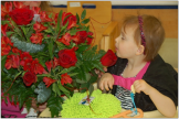 A child smelling flowers, engaging with the environment around her