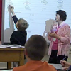 A child interacting with an electronic white board in the classroom